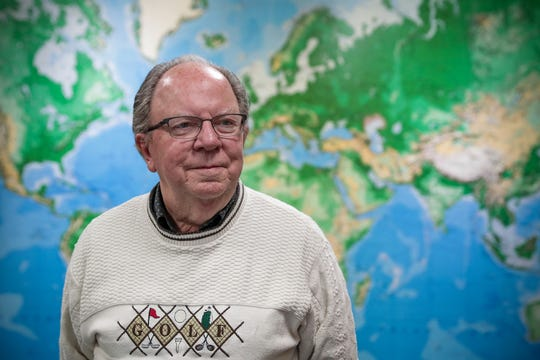 """Alex Kutin poses for a portrait at his travel agency Travel Leaders in Lawrence, Ind., on Saturday, March 14, 2020. """"It's an individual choice as to whether you want to go [on your trip] or not, but if you're someone who is elderly and has health issues, its probably best to go ahead and postpone it for a while,"""" Kutin said, speaking about effects of the coronavirus global pandemic."""