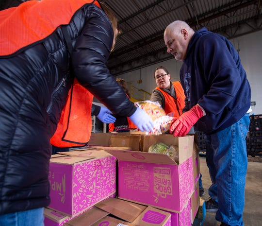 Volunteers load boxes of food into cars at Gleaners Food Bank of Indiana, Monday, March 16, 2020. The food bank set up a drive-thru distribution system at their westside facility in Indianapolis to enable the distribution of food.