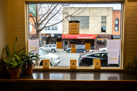Signs for Chomp delivery hang on the front window, Monday, March 16, 2020, at Nodo in downtown in Iowa City, Iowa.