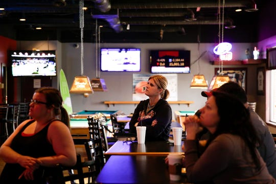 Owner Amy Morris watches Gov. Eric Holcomb speak during a press conference being televised on tv at the End Zone Sports Bar & Grill, Monday, March 16, 2020 in Lafayette.
