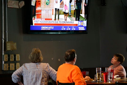 Nancy Lunger of Lafayette watches Gov. Eric Holcomb during a televised press conference at the End Zone Sports Bar & Grill, Monday, March 16, 2020 in Lafayette.