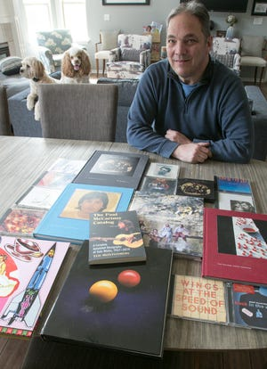 Ted Montgomery displays some of his Paul McCartney concert tour commemorative books and CDs, along with the book he published on the former Beatle, at his Green Oak Township home Monday, March 16, 2020. Behind Montgomery are his two rescue dogs, Boyd, left, and Maggie.