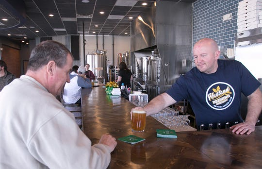 Hartland Brewing Company owner Ryan McDonald, right, serves customer Kurt Hartmann a Hop Dodger beer Monday, March 16, 2020 with St. Patrick's Day decor around the Hartland Township bar, taking advantage of pre-closing hours and trying to make the best of revenue that will be lost because of Gov. Whitmer's executive order.