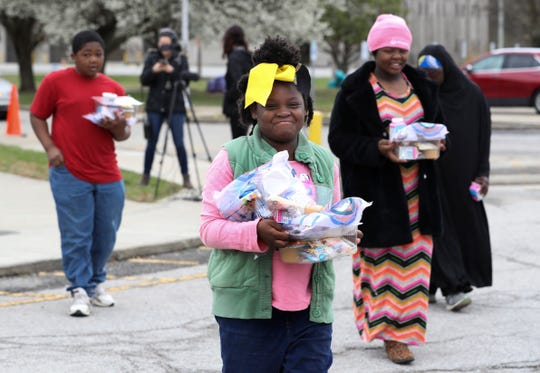 Samiha Stephens, 8, center, carries free lunches along with her brother, Sabir, 10, and sister, Tahirah, 9, after receiving them at Rangeland Elementary School on Monday.
