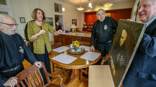 Gary Pitcock holds up a painting of Blessed Bernard Mary Silverstrelli and shows it to Angela Kwasinski and other members of the Passionists.