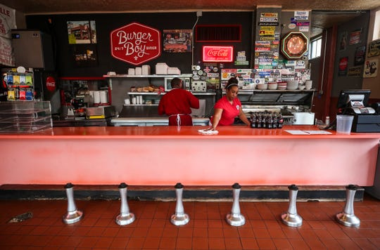 A Burger Boy employee wipes down the counter in front of stools that have had their seats removed as a cook prepares a carryout order Monday morning. Gov. Andy Beshear announced Monday that all restaurants and bars must close in-person service.