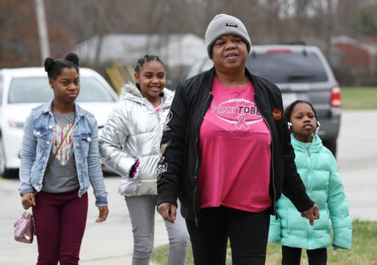 Angelina Johnson, second from right, was accompanied by her granddaughters and niece as they arrived to pick up free lunches outside Rangeland Elementary School on Monday.