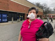 Patria Fielding sports a dust mask, to which she has stapled a Clorox wipe, as she prepares to shop for hand sanitizer at Kroger on Monday.