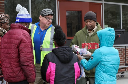Boyd Rouse, center, and Steve Shaw, right, (both facing camera) handed out free lunches to a family outside the Rangeland Elementary School in Louisville, Ky. on Mar. 16, 2020.  Jefferson County Public Schools will be providing the lunches to families with school age children while school is not in session due to the coronavirus outbreak.