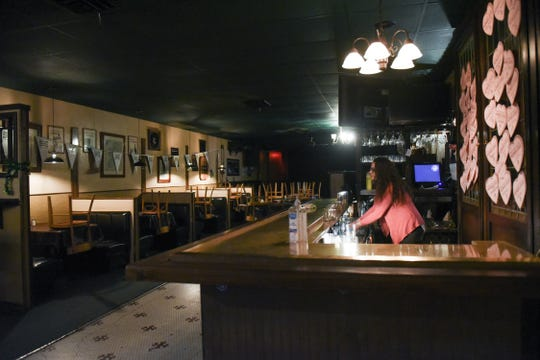 Moriarty's Pub bartender Annelise Hudson closes up the bar Monday, March 16, 2020, shortly after 3 p.m after Gov. Gretchen Whitmer ordered a halt to all dine-in service. Many restaurants are still providing carryout and delivery services.