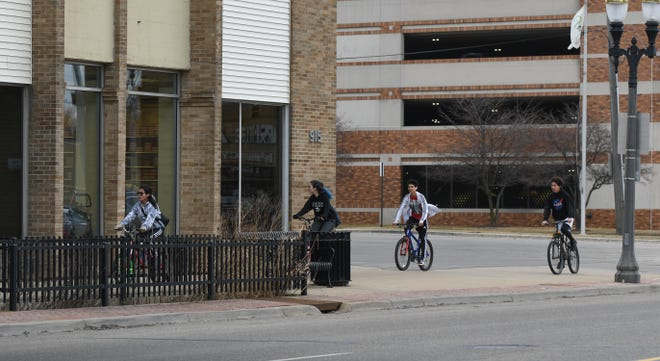 Youngsters ride their bikes along East Michigan Avenue near Pennsylvania Avenue on Monday afternoon, March 16, 2020.  Schools across the state have closed in a statewide push to mitigate the spread of the COVID-19 coronavirus.