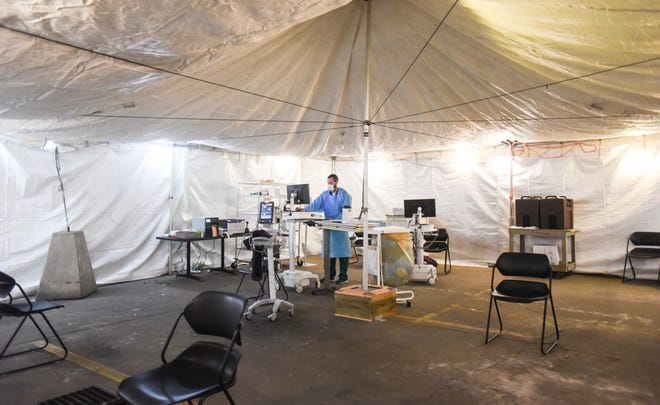 Ben Gwizdaia, a registered nurse at Sparrow Hospital in downtown Lansing, works in a screening tent set up in the parking ramp near the emergency room entrance on Monday, March 16, 2020.