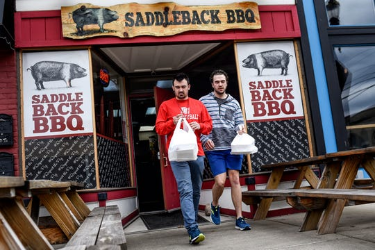 Gabe Murley, left, and Chris Croft leave Saddleback BBQ with their takeout orders on Monday, March 16, 2020, in Lansing. The two plan to continue to support local food establishments during the coronavirus restrictions that limits restaurants to takeout orders.