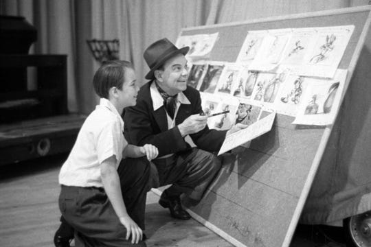 Dickie Jones and Cliff Edwards, who voiced Jiminy Cricket, look at a Pinocchio storyboard.