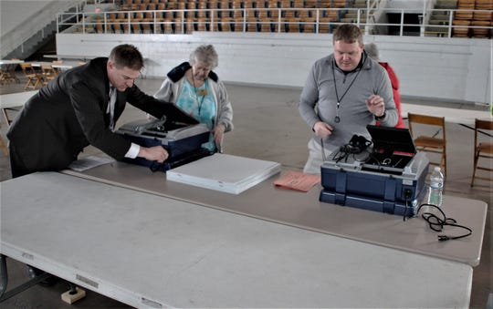 Marion County Board of Elections members Todd Anderson, left, and Chris Smith, center, help Deputy Director Brian Blair, right, set up machines on Monday at Veterans Memorial Coliseum in Marion ahead of Tuesday's primary election, which was delayed due to coronavirus concerns.