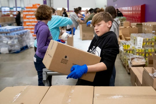 Rylan Faye, 12, of Collierville, moves a sealed box to a pallet Monday, March 16, 2020, at the Mid-South Food Bank in Memphis.
