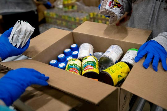 A box of food moves down the line Monday, March 16, 2020, at the Mid-South Food Bank in Memphis.