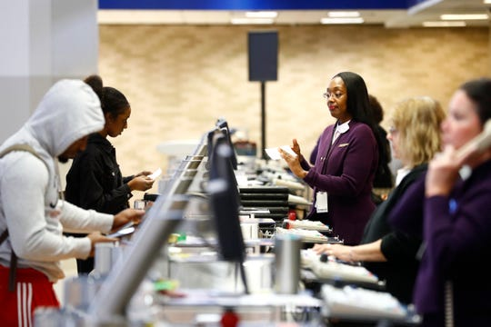Ticketing agents help travelers make their way through Memphis International Airport on Monday, March 16, 2020. Airport officials say that travel is down about 50% nationwide from this time last year, likely due to concerns over the spread of the coronavirus.