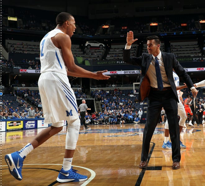 New Rhodes men's basketball coach Steven Goodson, who served as the Tigers' director of basketball operations under Tubby Smith, celebrates with former Memphis forward Jimario Rivers (left).