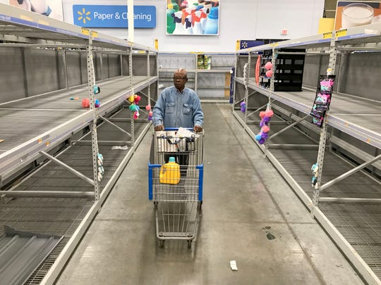 A shopper moves his cart in an aisle that's normally stocked with toilet paper and other paper products at Walmart on W. Brown Deer Rd. in Brown Deer on Monday, March 16, 2020.  The impact of the coronavirus pandemic is causing area store's paper stock to become depleted.