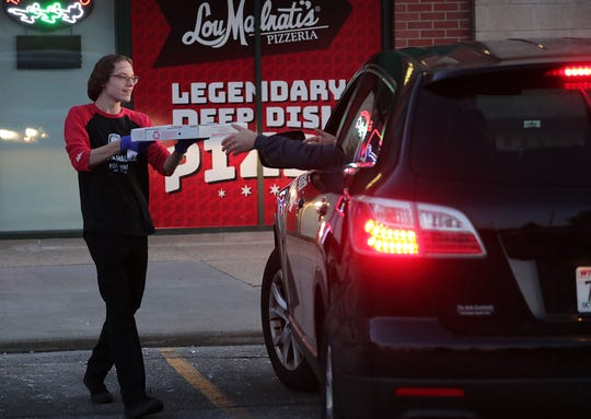 Langdon Oldenburg takes a pizza to a customer's car at Lou Malnati's Pizzeria in Fox Point on Sunday. The carryout pizza restaurant is offering curbside delivery to reduce the spread of the coronavirus.