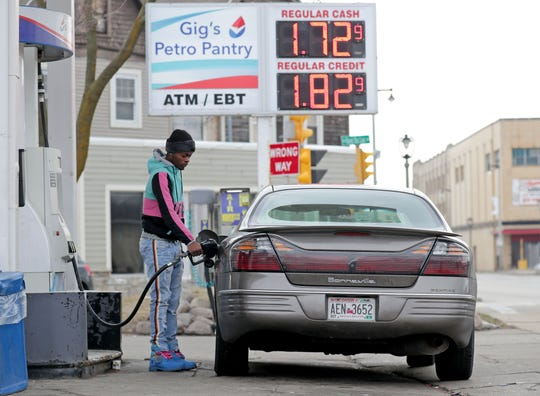 Desmond Williams, of Chicago, gets gas for $1.72 a gallon for cash and $1.82 for credit at Gigs Petrol Pantry on West Fond du Lac Ave. in Milwaukee on Monday. The impact of the coronavirus pandemic is effecting all sectors of the economy, including the price of crude oil.
