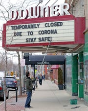 Rashad Kraima, general manager of Landmark's Downer Theatre on North Downer Avenue in Milwaukee, posts a sign on the marquee notifying guests of the movie theater's closing due to the coronavirus.