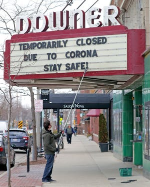 Rashad Kraima, general manager of Landmark's Downer Theatre on North Downer Avenue in Milwaukee, posts a sign Monday on the marquee notifying guests of the movie theater's closing due to the coronavirus.