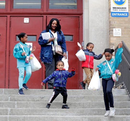 """I want to thank MPS for providing meals and especially for providing homework, that's a plus,"" says Nia Ramirez as she and her four children who attend ALBA Elementary School head home after receiving their meals Monday."