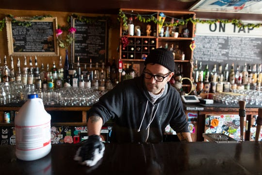 BJ Seidel uses bleach to clean Burnhearts, the bar he co-owns with his wife, Monday, March 16, 2020, at 2599 S. Logan Ave. in Milwaukee.