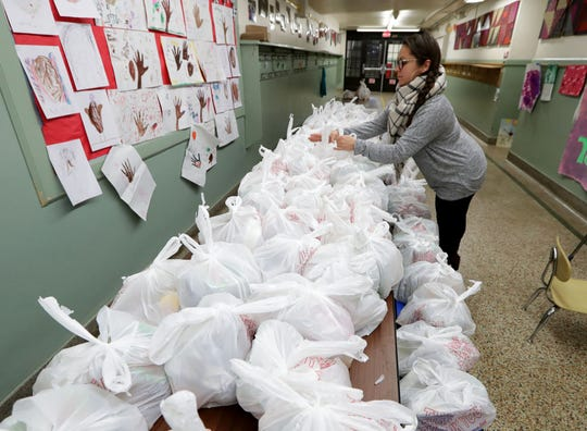 Clarissa Ramos, an MPS Headstart supervisor, organizes meal bags to be handed out at Barbee Montessori School on North Teutonia Avenue in Milwaukee.