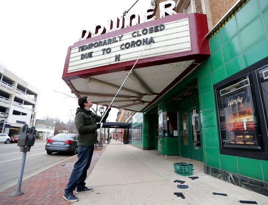 Rashad Kraima, Landmark Downer Theatre general manager, posts a sign on the marquee notifying guests of the movie theater's closing due to the coronavirus Monday.
