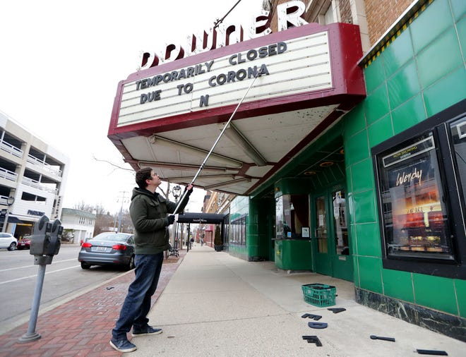 Rashad Kraima, Landmark Downer Theatre general manager, changes the movie theater's marquee to reflect the new normal for theaters in the coronavirus pandemic. The Downer closed Monday, one of several theaters that closed ahead of the state's order barring gatherings of 10 or more people.