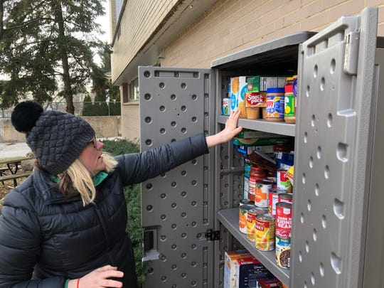 Amber Stroud, who helped start a pop-up food pantry outside of Jefferson Elementary in Wauwatosa, helps rearrange items in the pantry.