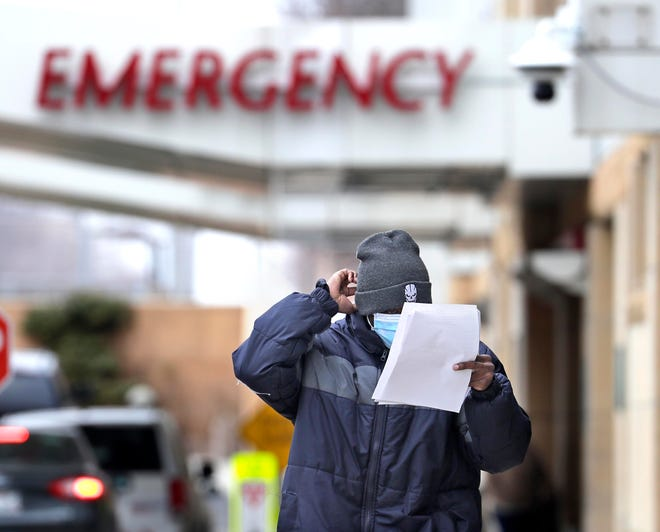 A person with a mask leaves the Aurora Sinai Medical Center Emergency Department in Milwaukee. Recently the hospital had a tent set up next to the ambulance bay of the emergency department. Several security personnel and a medical professional were stationed at the tent.