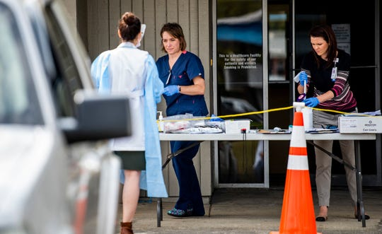 Clinic staff work triage as the check on possible patients in cars at Baptist Health's Coronavirus Care Clinic that is now open in Montgomery, Ala., on Monday March 16, 2020.