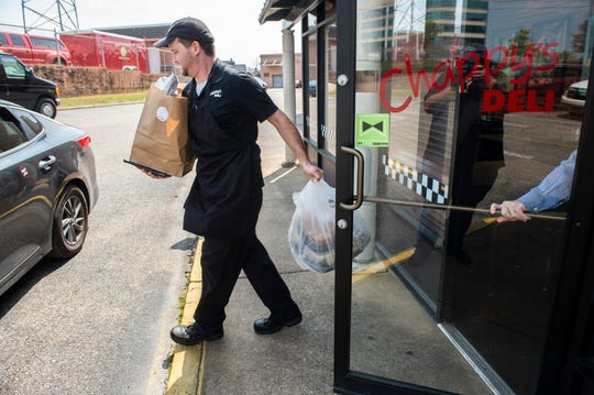 Jimmy Griggs heads out on a food delivery at Chappy's Deli on Perry Hill Road in Montgomery, Ala., on Monday, March 16, 2020.