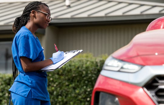 Clinic staff talk with possible patients in cars at Baptist Health's Coronavirus Care Clinic that is now open in Montgomery, Ala., on Monday March 16, 2020.