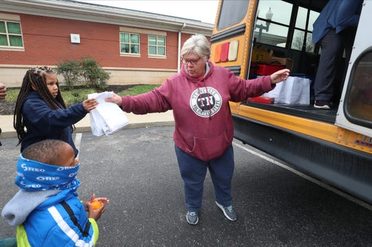 "Leanne ""Big Momma"" Alsup, a Murfreesboro City Schools bus driver, hands out breakfast to Anastasia Patton, 7, and Andrew Patton, 4, during a stop at the Rutherford County Health Department in downtown Murfreesboro on Monday, March 16. While schools are closed out of concern over the coronavirus pandemic, city schools have deployed CHOW buses and regular school buses to provide kids with breakfast and lunch."