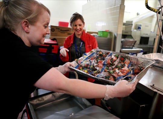 Brandy Smotherman, assistant cafeteria manager at Discovery School at Bellwood, left, and bus driver Joann Thompson unpack unused breakfast items before packing up lunch at Reeves-Rogers Elementary on Monday, March 16, 2020.