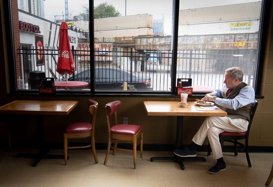 Mark Reagan enjoys his lunch at Arnold's Country Kitchen on Monday in Nashville. The popular meat-and-three spot saw only about one-fourth its normal crowd for lunch Monday because of concerns about the coronavirus outbreak.