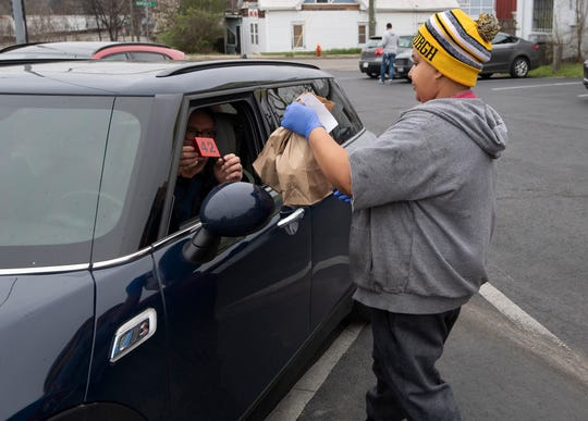 Gabby's Burgers & Fries employee Margaret Rogers (rt) delivers food to Steve Lojacono in his car Monday, March 16, 2020 in Nashville, Tenn. Gabby's Burgers & Fries has shutdown its dining room and only serving take-out food to their customers in the wake of the coronavirus outbreak.