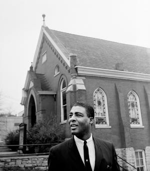 The Rev. Kelly Miller Smith, pastor of First Baptist Church, discusses plans April 4, 1964 for building a new structure at the present church site, 319 Eighth Ave., N. Behind him is the historic, 69-year-old church building that will be razed when the new one is constructed.