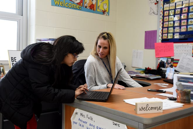 Just prior to Newark City Schools buildings closing in March, Carson Elementary third grader Selena Uballe finished a math assessment and got worksheets to take home from teacher Jennifer Fulk.