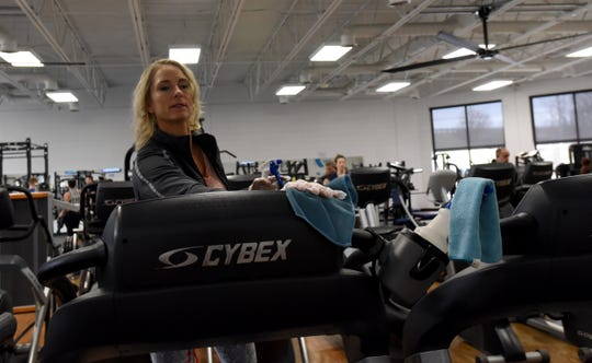 Licking County Family YMCA fitness attendant Trish Harrison cleans exercise equipment in the main gym. Ohio governor Mike DeWine closed gyms and bowling alleys during a press conference on Monday, March 16, 2020.