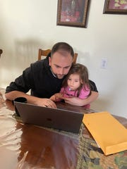 Francesco Fasolo, a sixth-grade history teacher in Garfield, watches his niece while he fields questions from students on the first day of remote learning. March 16, 2020.