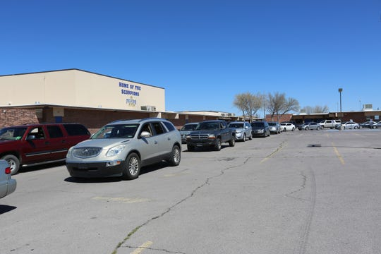 Two rows of vehicles circle the parking lot at Pichacho Middle School, Monday March 16, 2020, as parents wait to get free lunch for their students.