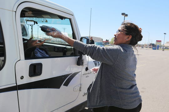 Erika Washburn helps to distribute free lunch to schoolchildren at Picacho Middle School on Monday March 16, 2020.