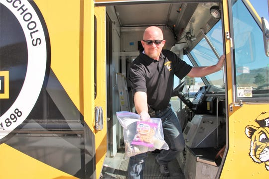 Alamogordo Public Schools Superintendent Jerrett Perry hands off a grab and go meal pack  from the APS food truck March 16.  Monday, March 16 marked the first day of canceled classes due to COVID-19 in the Alamogordo Public School District.