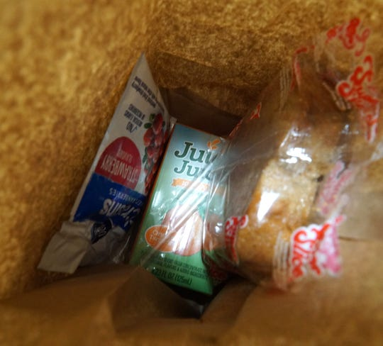Some dried fruit, a juice box and slice of bread are part of a take-home breakfast for Huron Valley students during their school closure.